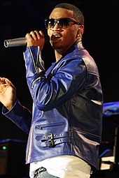 A man wearing a blue jacket holding a microphone