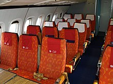 The passenger cabin of an airliner with orange-coloured seats and blue carpeting, the cabin is illuminated by daylight from the windows.