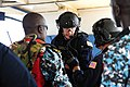 U.S. Coast Guard Maritime Enforcement Specialist 1st Class Scott Easley, center, and Chief Maritime Enforcement Specialist Rob Wills, center right, both with the Maritime Security Response Team, confer with 120620-N-GN377-030.jpg