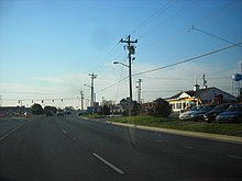 A divided highway approaching a signalized intersection with DE 24, which is marked on a small sign to the right of the roadway
