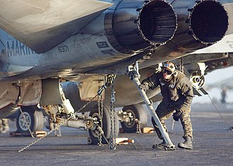 Tailhook - Maintenanceman inspects an F/A-18 tailhook prior to launch.
