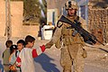 US Navy 061219-M-9019H-065 Lance Cpl. Jacob E. Nation from Elizabethtown, Ill., assigned to the 2nd Battalion, 3rd Marines (2-3) greets Iraqi children as he patrols through the city of Haqlaniyah, Iraq.jpg