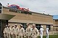 US Navy 070508-N-0975R-001 Seabees from Naval Mobile Construction Battalion (NMCB) 18 stand by while the ensign is lifted to reveal the newly named Charles V. Komppa wing in honor of the Seabee that died in Iraq, Oct. 25, 2006.jpg