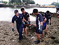 US Navy 070720-N-7109S-001 Sonar Technician 2nd Class James Burns, stationed aboard guided-missile frigate USS Jarrett (FFG 33), helps members of the Republic of Singapore navy remove debris from the inland waterways.jpg