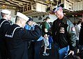 US Navy 071216-N-0916O-036 Storekeeper 1st Class Rick Belarmino salutes civilian personnel as they board the nuclear-powered aircraft carrier USS Enterprise (CVN 65) during a stop at Naval Station Mayport.jpg