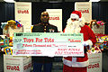 US Navy 081218-N-6981B-006 Gunnery Sgt. Theodis Jones accepts a $15,000 check for the U.S. Marine Corps annual Toys for Tots campaign.jpg