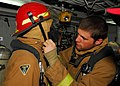 US Navy 100217-N-7918H-071 Sailors assigned to repair locker 2 aboard the amphibious dock landing ship USS Ashland (LSD 48) help each other secure their firefighting gear during a fire drill in the main machinery room.jpg