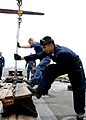 US Navy 100702-N-3327M-012 Aviation Boatswain's Mate (Equipment) Airman Milton Arevalo and Aviation Boatswain's Mate (Equipment) 3rd Class Aaron Patterson emoves a catapult deck-plate prior to maintenance.jpg