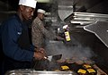 US Navy 110406-N-QP268-107 Culinary Specialist 1st Class Victor Mitchell and Sgt. Evan Westpfahl prepare grilled hamburgers for Sailors and Marines.jpg