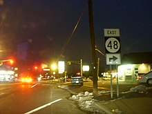 A nighttime view of a road lined with businesses approaching a traffic light. A sign on the right side of the road reads east Route 48 right.