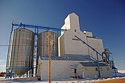 Grain elevator on snow, against a blue sky