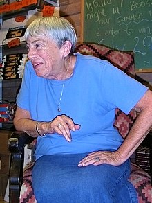 A photograph of a woman sitting in a chair, leaning on its armrest with her right arm, and looking over the armrest while wearing a blue shirt