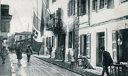 Italian soldiers in Vlore, Albania during World War I. The tricolour flag of Italy bearing the Savoy royal shield is shown hanging alongside an Albanian flag from the balcony of the Italian headquarters. Vlora zur Zeit der italienischen Besatzung 1916-1920.jpg