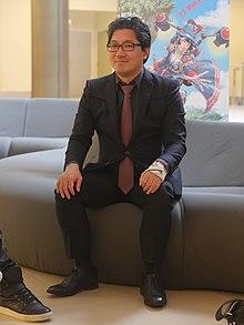 Photo de Yuji Naka, souriant et assis sur un canapé, en costume noir