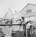 'Afhalers' zwaaien met een zakdoek vanachter hekken op de kade in de haven, Bestanddeelnr 255-2182.jpg