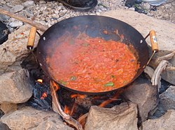 Qalayet Bandora kookte boven een kampvuur in Wadi Mukheiris, vlakbij de Jordaanse kust van de Dode Zee.