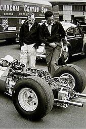 John Surtees et l'ingénieur Mauro Forghiri marchant dans les stands.