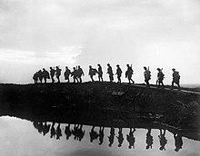 Soldaten gehen uber Entenbretter uber einem wassergefullten Muschelkrater