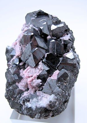 Alabandite - Group of octahedral alabandite crystals partially coated with pink rhodochrosite, from Uchucchacua Mine, Oyon, Lima, Peru (size: 60 mm x 59 mm x 46 mm, 204 g)