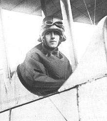 Half-portrait of man in flying helmet and goggles seated in the open cockpit of a biplane