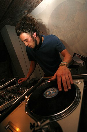 Disc jockey - A DJ performing at an event using record turntables and a DJ mixer, a small mixer used to transition between songs.