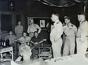 Ten men in military uniforms and fatigues talking in a room