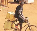 A Young Man caring Jerrycans on Bycycle to fetch water for a living.jpg