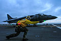 A flight deck crewman clears an AV-8B Harrier to take off during flight operations aboard the amphibious assault ship USS Boxer (LHD 4) as the ship conducts training in the Pacific Ocean 130325-N-CD336-235.jpg