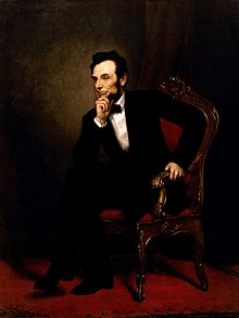 A painting depicting President Lincoln seated in an ornate wooden armchair.  He wears a black suit and bow tie.  He is leaning forward, legs crossed, with one hand on his chin.