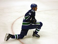 An ice hockey player dressed in a blue jersey with blue and green trim. He is stretching with one knee on the ice and the other lunged forward. He rests his stick on one leg while looking forward.