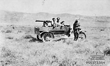 An armoured car showing the driver standing beside the car, passenger sitting in the car with a machine gun and gunner.
