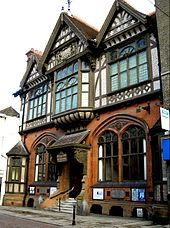 Half-timbering, Gothic Revival tracery and Jacobean carved porch brackets  combine in the Tudor Revival Beaney Institute, Canterbury (1899)