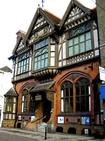 Half-timbering, Gothic Revival tracery and Jacobean carved porch brackets combine in the Tudor Revival Beaney Institute, Canterbury (1899) Beaney Institute 002.jpg