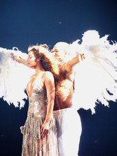 Knowles, wearing, a silver dress is being hugged from behind by a shirtless man donning white trousers and large feathered wings.