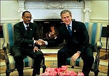 Kagame vistiendo un traje y la insignia de la bandera de Ruanda durante una reunión con el presidente estadounidense George W. Bush