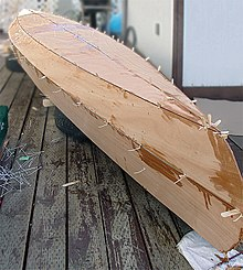 A stitched canoe hull under construction.