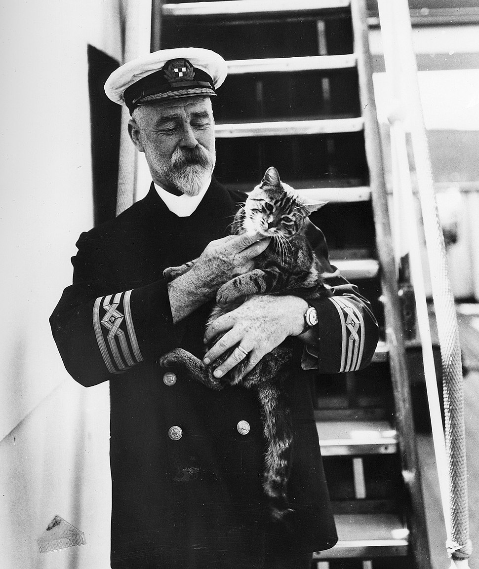 Captain A. J. Hailey in uniform with a cat on the first C.P. R.M.S. Empress of Canada