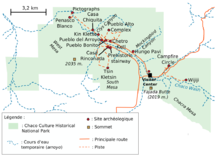 "A large green area representing Chaco Culture National Historical Park's boundaries sits in the middle of a white field. The green area is roughly rectangular with one smaller square-like and one triangular appendage abutting it at bottom-left and bottom-right, respectively. Fifteen small red circles represent the location of important Chacoan sites; they are focused on a line running from top-left (northwest) to bottom-right (southeast). A dashed blue line depicting the Chaco Wash runs roughly along the same line; a network of dashed and solid orange lines represent trails and metalled roads, respectively, also focus on the same axis, connecting the red dots. Two gold squares define high points: ""Fajada Butte (2019 m.)"" and ""West Mesa (2035 m.)""."