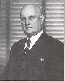 An unsmiling balding white man in a three piece suit