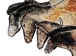 Prehistoric drawing showing the heads and fore quarters of four horses, drawn in black and ocher