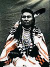 American Indian male sitting with one feather in hair and wrapped in a patterned blanket