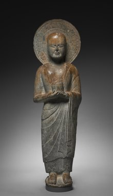 Monk holding cylinder-shaped object. Monk is depicted with aura-like shape around the head