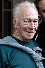 Upper torso of a gray-haired old man. He is wearing a teal T-shirt with a grey sweater tied around his neck