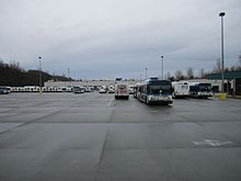 A large, paved parking lot with buses parked in rows