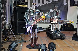Compressorhead - Fingers on Gibson Flying V, Bones on Fender Precision Bass - Musikmesse Frankfurt 2013.jpg