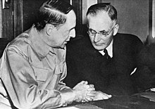 MacArthur (in a military uniform) and Curtin (in a dark suit) sitr at a table. Curtin is leaning towards MacArthur, listening.