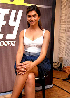 Deepika Padukone is sitting on a chair and smiling at the camera