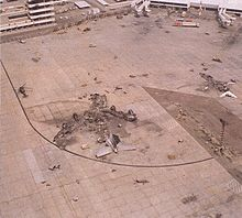 Wreckage in outline of burned-out aircraft; only the tail assembly is intact