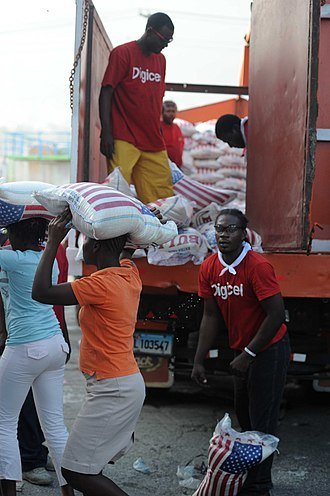 Digicel - Volunteers from Digicel distributed several tons of food to Haitian citizens in Port-au-Prince, in a distribution sponsored by the Agency for Technical Cooperation and Development following the devastating 2010 Haiti earthquake.