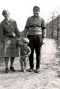 a man, wearing a striped sweater and trousers and a hat, with a woman, wearing a skirt and a cardigan, holding the hand of a boy wearing shorts, on a walking path